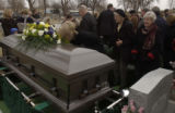 left center at coffin, Cynthia Gray, daughter of Harold, leans in at the end of the ceremonies at...