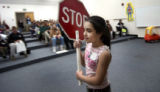 Michelle Gabriella Gonzalez, 8, carries a Stop sign in front of a group of parents and community...
