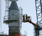 Workers on a lift attach a cage ladder to  the Tailgas Unit on the Suncor Refinery site in...