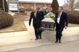 Tim White, left and Neal White, right, lead the casket to the hearse from the church. Harold...