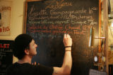 Patrick DuPays (cq), owner and chef of Z Cuisine Bistrot (cq), writes the evening's menu on the...