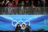 U.S. skater Johnny Weir (bottom center) waits to hear his scores after the Men's Free Skating...