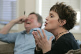 Jeff Allen (in background) laughs as he and his wife Patti Allen discuss the political dynamics in...