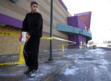 Rodney Cusick, 17, spreads salt on ice that formed outside Century Theaters after a water pipe...