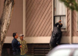 Denver, Colo., photo taken June 17, 2004- Glendale police investigators examine a window at the...