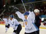 Team Finland's Ville Peltonen (center) celebrates a goal by teammate Olli Jokinen (not pictured)...