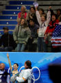 Fans cheer as the score for U.S. figure skater Sasha Cohen (bottom left) is announced after the...