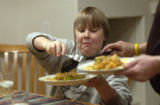 **FOR SPOTLIGHT** Michael Glantz, 13, gets a second helping of paella during dinner at the...