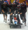 Steven Holcomb, front right, Curt Tomasevicz (right, behind Holcomb), Bill Schuffenhauer, left,...