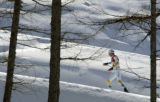 Johan Olsson, of Sweden, skis through the trees in the men's 50KM Cross Country Mass Start in...
