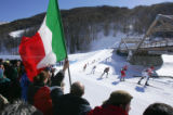 A fan holds an Italian flag as a line of skiers tuck as they go down a hill in the men's 50KM...