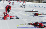 A group of skiers collapse in exhaustion at the finish of the men's 50KM Cross Country Mass Start...