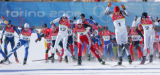 Skiers sprint at the start men's 50KM Cross Country Mass Start in Pragelato Plan, Italy on Sunday,...