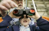 Shawn Bouchard, 8, gets help from DOW volunteer Ray Andrews on how to use binoculars. Third-grade...