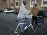 Univeristy of Colorado senior Kur Kur (l), a refugee from Southern Sudan, shakes hands with his...