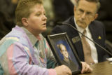 Erin-Lea Hanson, cq, shows a photograph of her daughter Amanda Lynn, to House Judiciary Committee...