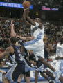 Denver Nuggets forward Ruben Patterson, middle, shoots over Memphis Grizzlies Dahntay Jones, left,...
