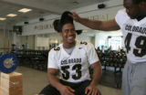 University of Colorado football player Thaddaeus Washington, cq, #49 checks out the hair of...
