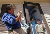 KAS057 Adams County democratic senate candidate Val Vigil, left, picks up a dog belonging to Fran...
