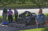 Police officers prepare to move the body of the driver of a fatal one vehicle car crash near the...