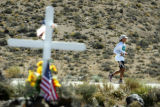 Eric Pence, of Eagle, Colo., runs past a memorial cross near Darwin Turnoff while running in...
