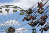 "Guests at Six Flags Elitch Gardens ride on the ""Turn of the Century"" ride with the..."