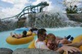 Guests ride on innertubes on the Castaway Creek ride at Six Flags Elitch Gardens in Denver, Colo.,...