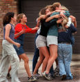 A student just evacuated from the school is embraced by friends overjoyed she is safe.